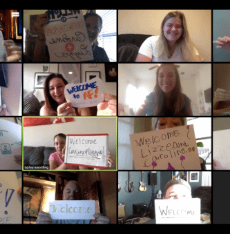 Virtual welcome for summer interns wit people holding signs on a Zoom eeting