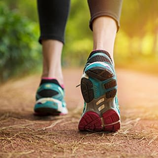 Woman in running shoes on nature path